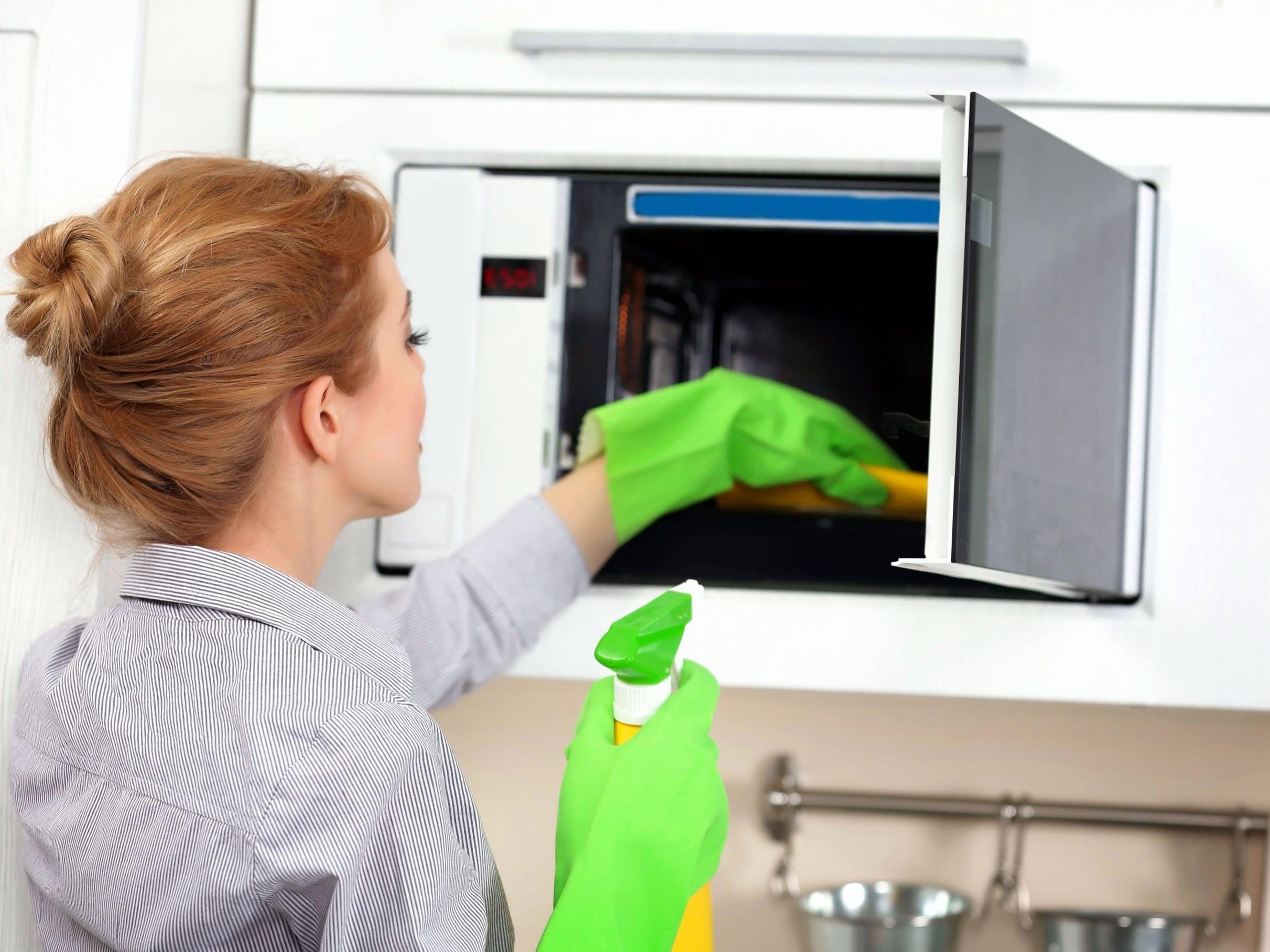 Девушка моет микроволновку